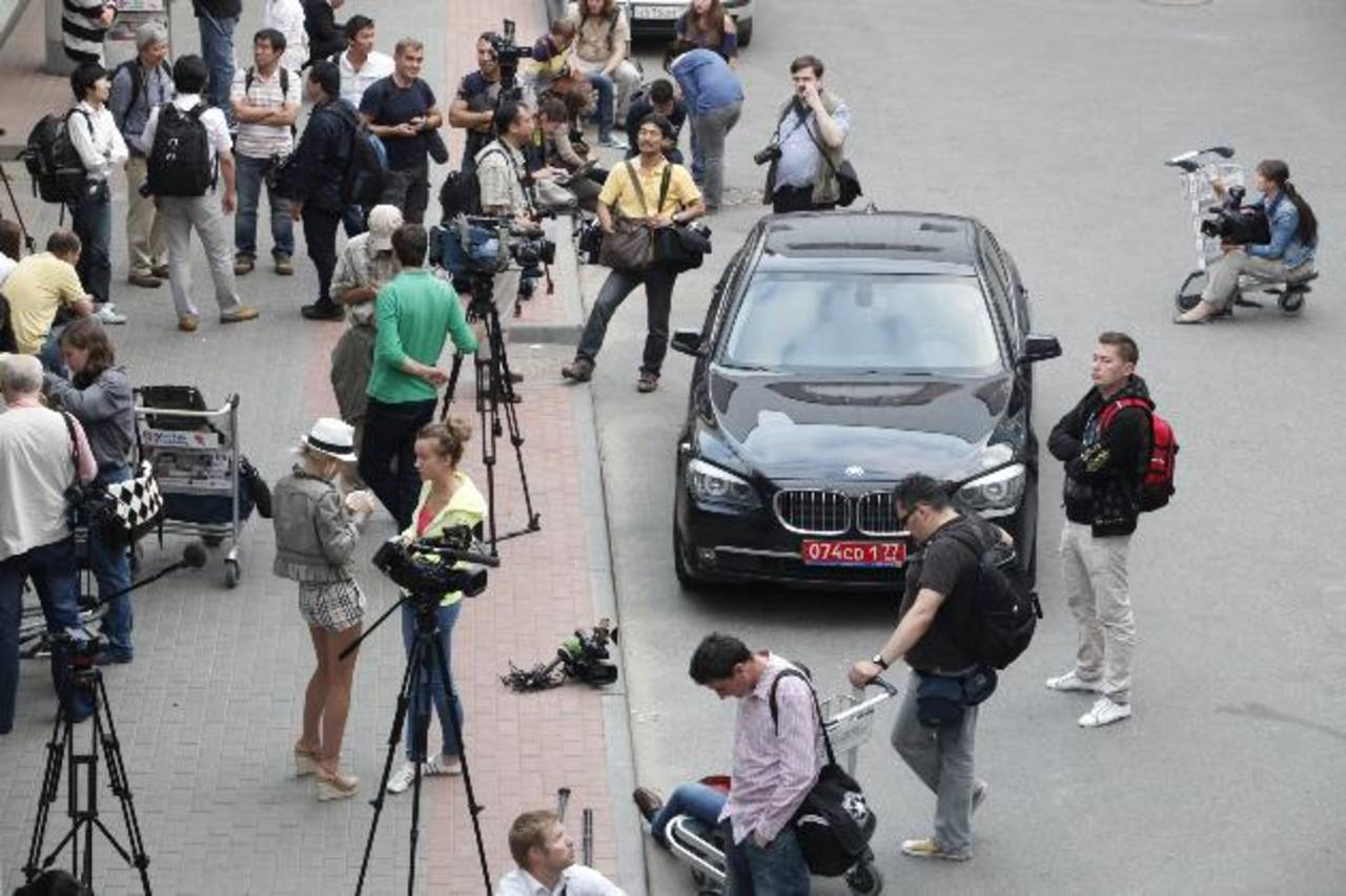 Periodistas esperan frente al vehículo del embajador de Ecuador, pendientes de noticias sobre Snowden. FOTO AP