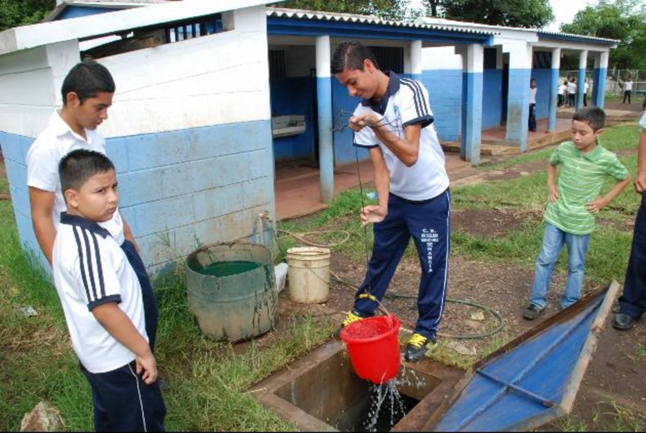 El agua que obtienen en el centro escolar Anselma Sánchez de Mancía no es apta para el consumo de los alumnos. Un profesor vigila que nadie la ingiera. Foto EDH / CRISTIAN DÍAZ