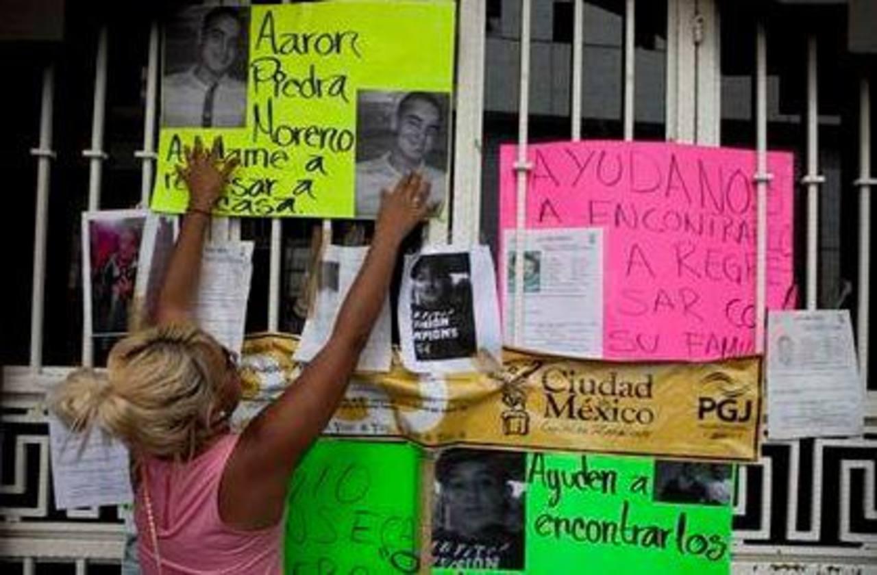 Una mujer coloca fotos en la entrada de un bar donde se produjo un secuestro masivo en la Ciudad de México. Foto/ AP