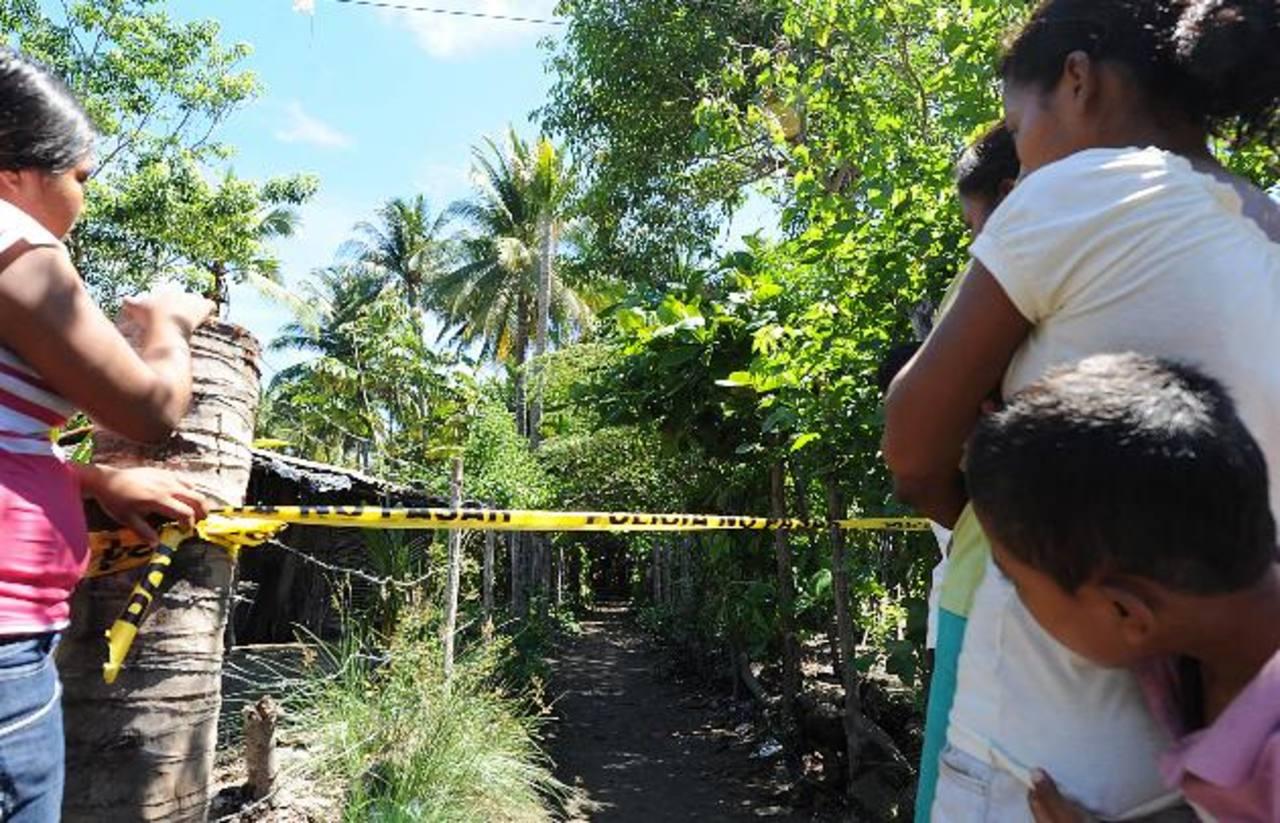 Vecinos y familiares observan el procedimiento policial en la escena donde fue asesinado Ricardo Toloza, de 17 años, en San Luis La Herradura, La Paz. Foto EDH / Claudia Castillo