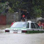 Los hombres empujan un taxi atrapado en una carretera inundada en Xalapa, capital del estado de Veracruz. Foto/ Reuters