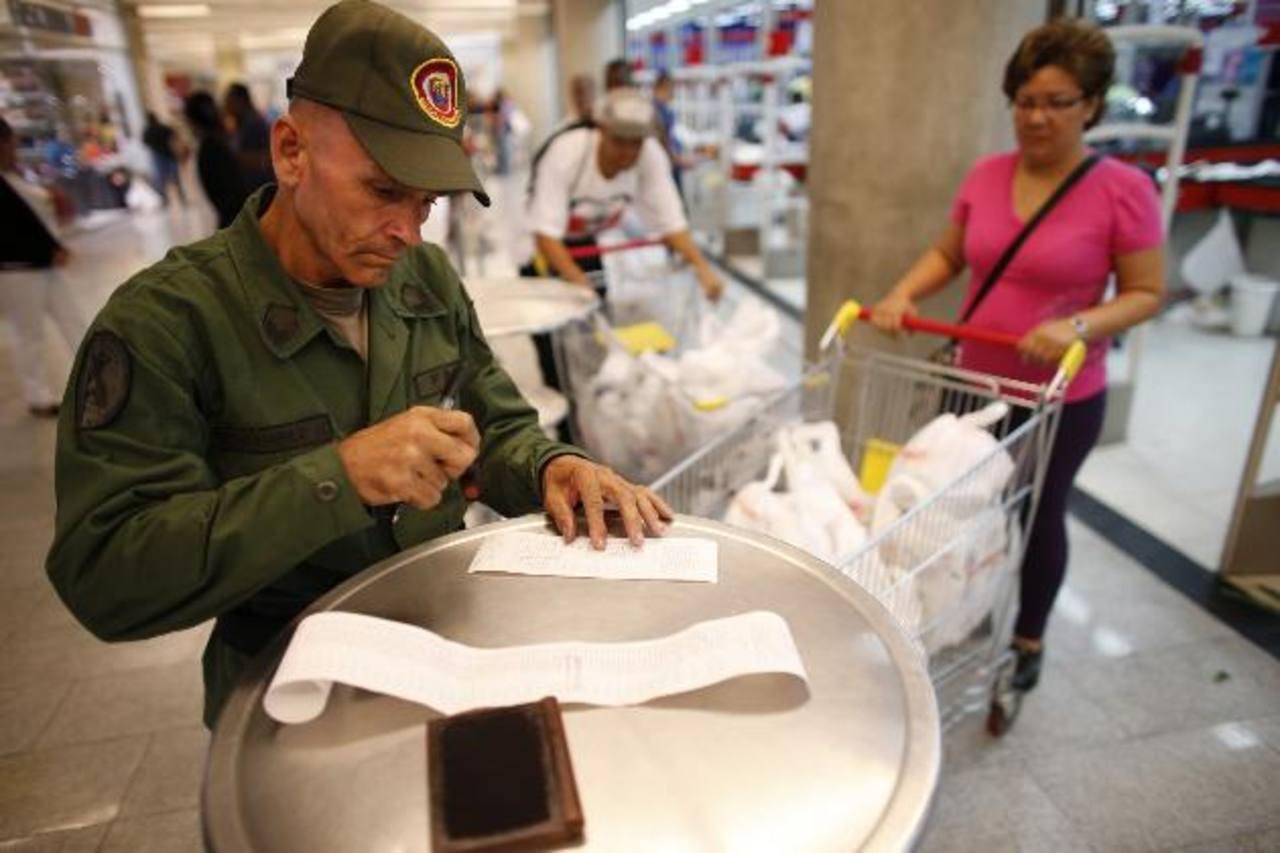 Un reservista del ejército comprueba un tíquet a la salida del supermercado estatal Bicentenario en Caracas. foto edh / reuters