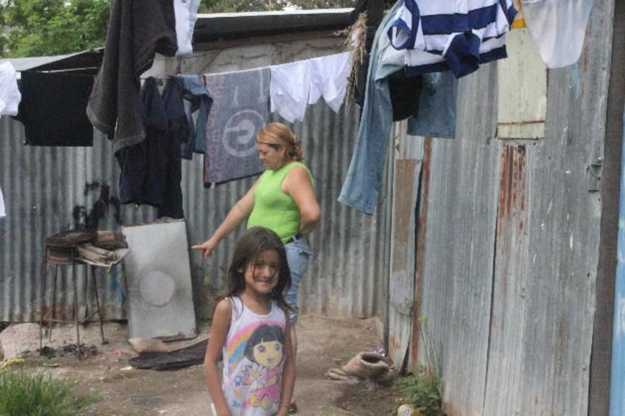 Paredes de lámina, piso de tierra y en un ambiente insalubre viven las 120 familias. Ellas siguen esperando las casas prometidas por el mandatario Funes. Foto EDH / Cortesía