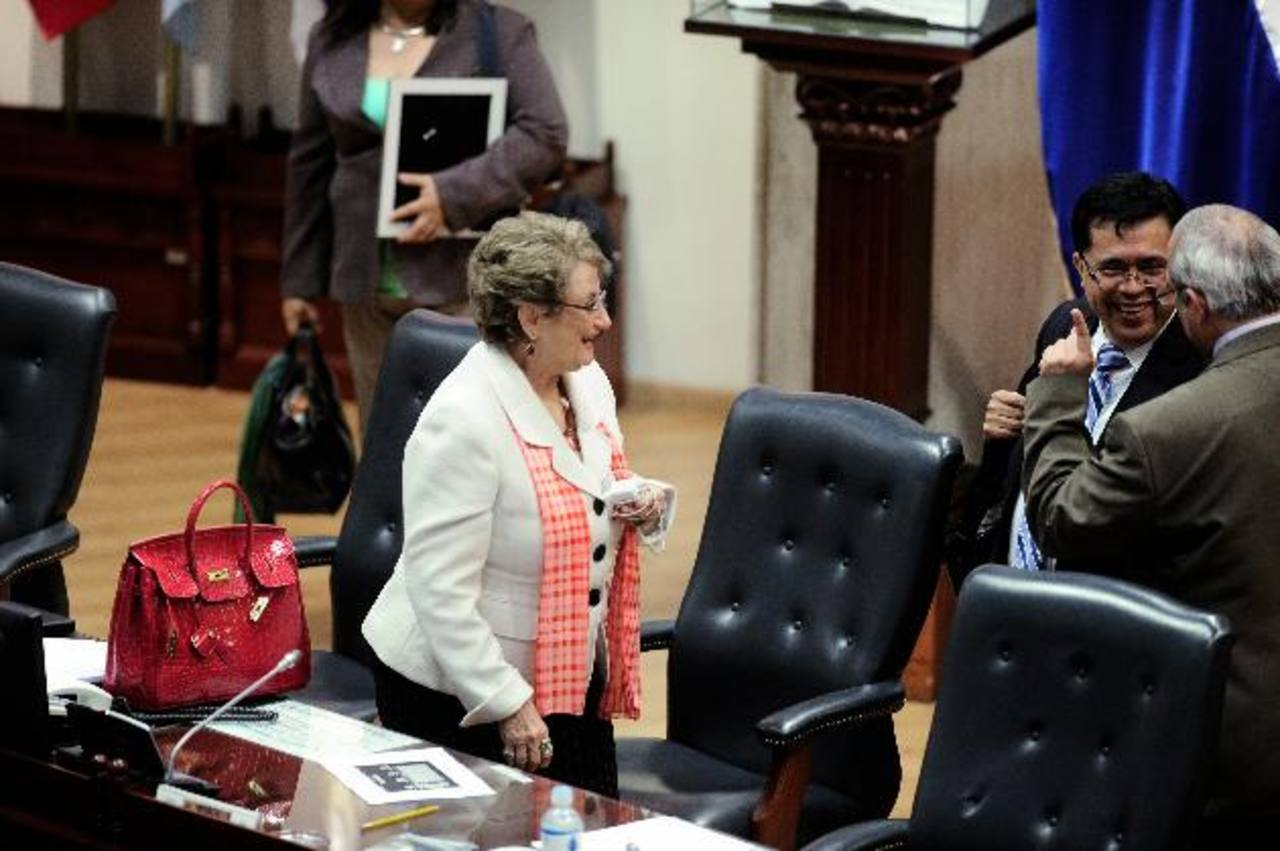 La diputada Carmen Elena de Escalón observa a sus colegas del FMLN, Roberto Lorenzana y Sigfrido Reyes, tras el receso de la plenaria. foto edh / jorge reyes