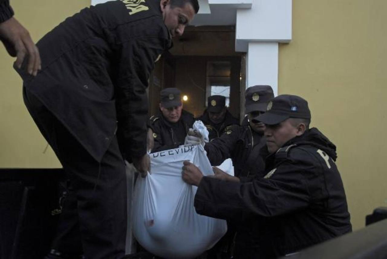 Agentes cargan el cuerpo de uno de sus compañeros.