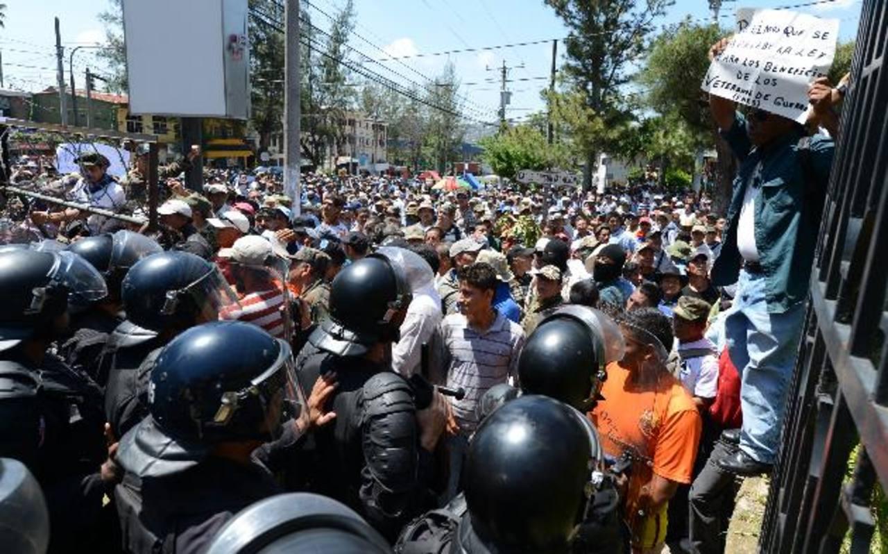 Cientos de veteranos de guerra que pretendían llegar a un hotel fueron bloqueados por la Policía. Foto EDH / Mauricio Cáceres.