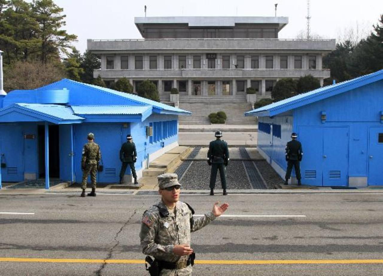Soldados surcoreanos (de espaldas a la cámara) observan a un soldado norcoreano (al fondo, entre las columnas) en la zona desmilitarizada en Panmunjom (Corea del Sur). foto edh / EFE.
