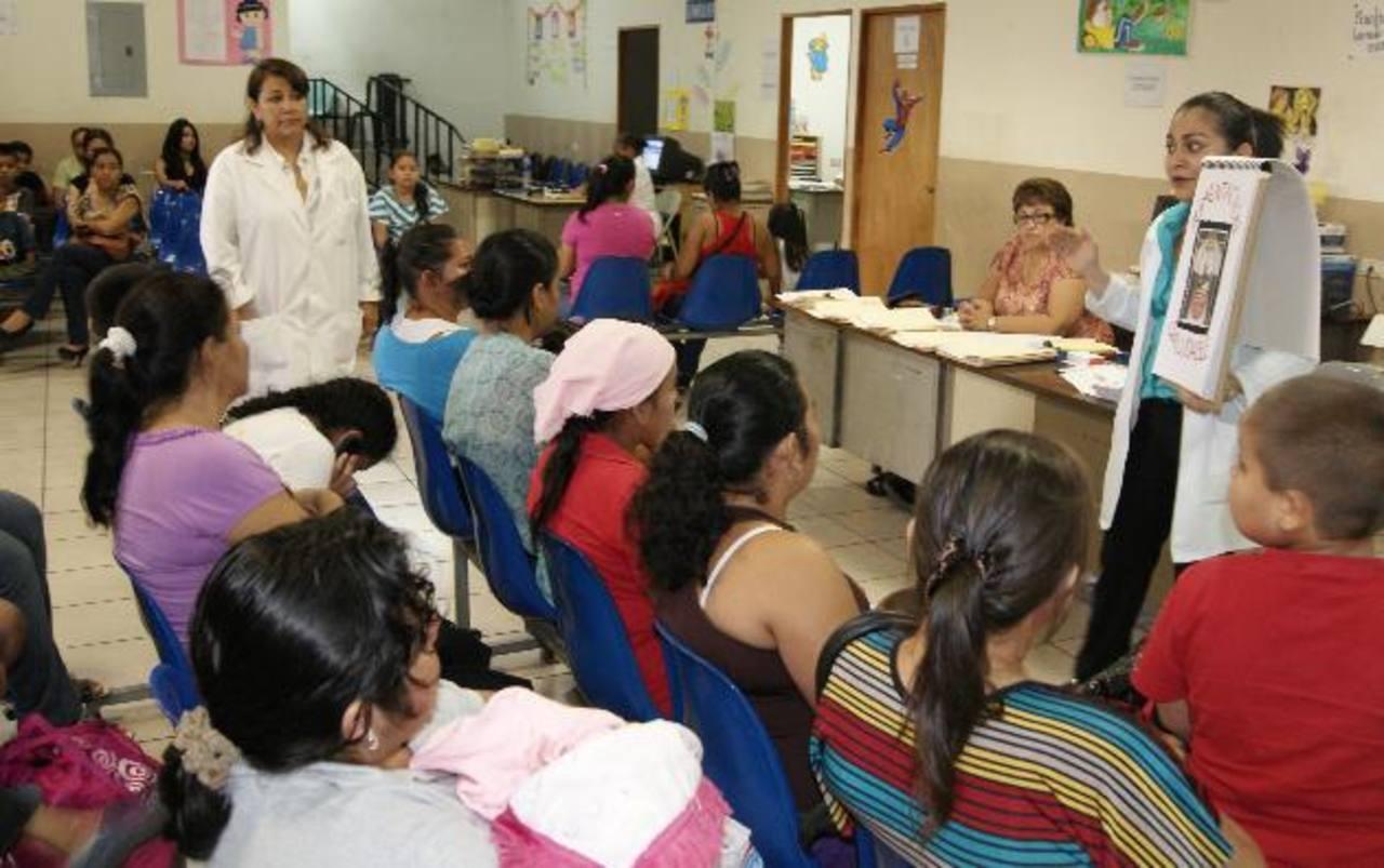 Madres de familia y algunos niños escuchan a la nutrióloga pediatra explicarles por qué se da la obesidad infantil y cómo evitarla. Coto EDH / Cortesía