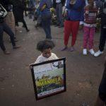 Una niña de muestra una imagen del ex presidente sudafricano, Nelson Mandela, en las afueras del hospital donde permanece ingresado el ex mandatario. Foto/ AP