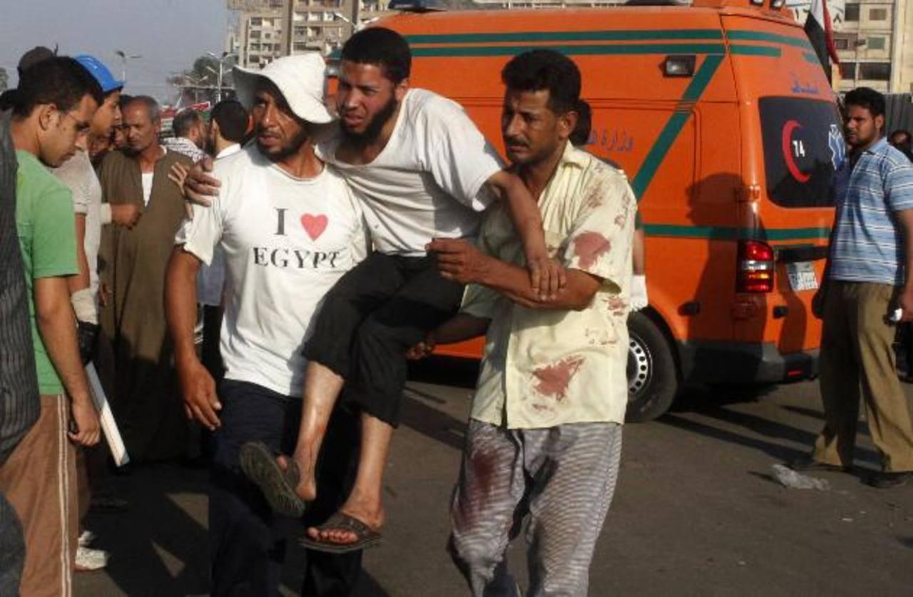 Un grupo de partidarios del presidente Morsi ayudan a uno de los heridos durante los enfrentamientos. FOTO rEUTERS