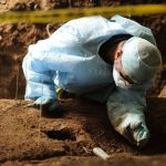 El criminólogo de la Fiscalía, Israel Ticas, trabaja en la exhumación de los cuerpos de las estudiantes. Foto EDH / Archivo