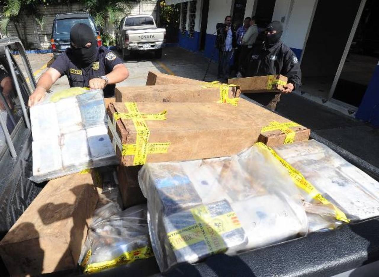 Agentes cargan la droga a un carro policial para ser llevada al laboratorio. Foto EDH / Marlon Hernández