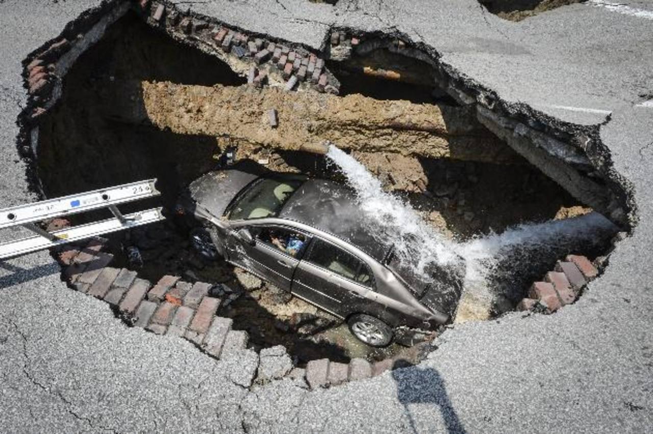 Un automóvil cayó en el fondo de un socavón causado por la ruptura de una tubería de agua. Foto/ AP