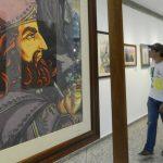 Jóvenes estudiantes de la Universidad Don Bosco pasan frente al autorretrato de Salarrué. fotografías edh/ marvin recinos