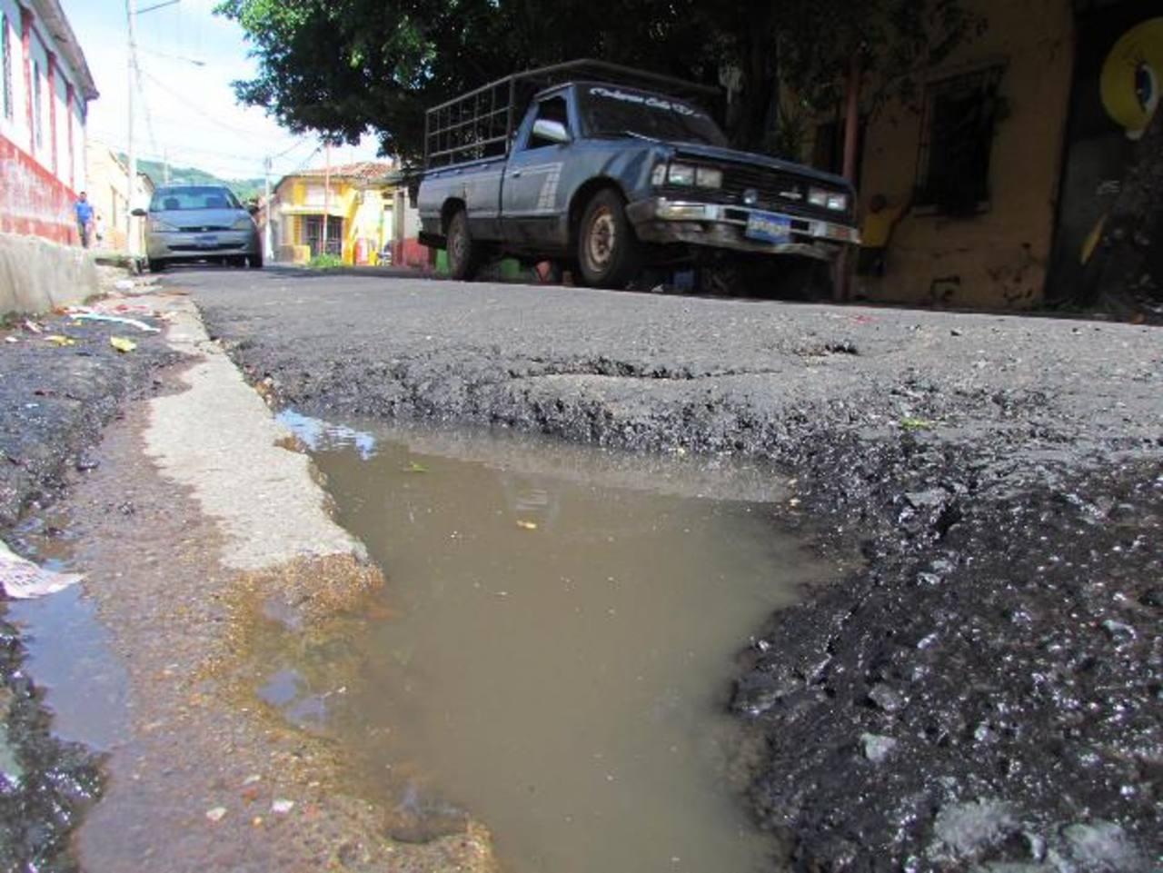 Una fuga de agua ha deteriorado la capa asfáltica en un tramo de la vía por la que a diario transitan numerosos vehículos particulares, buses y camiones. Foto EDH / Mauricio Guevara