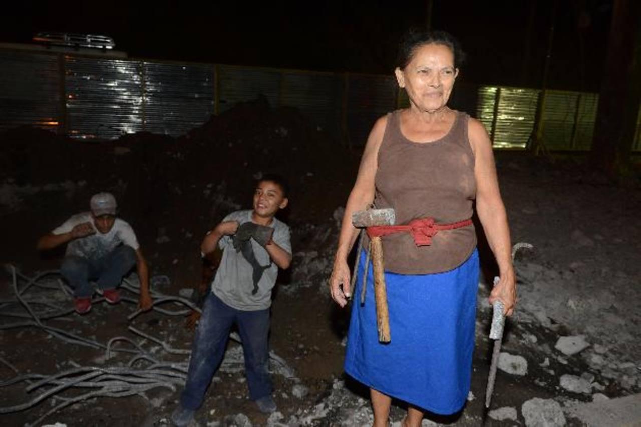 Grupos familiares tratan de obtener hierro para venderlo. Una ciudadana, almádana a la cintura, acumula las varillas obtenidas. Fotos edh / miguel villalta