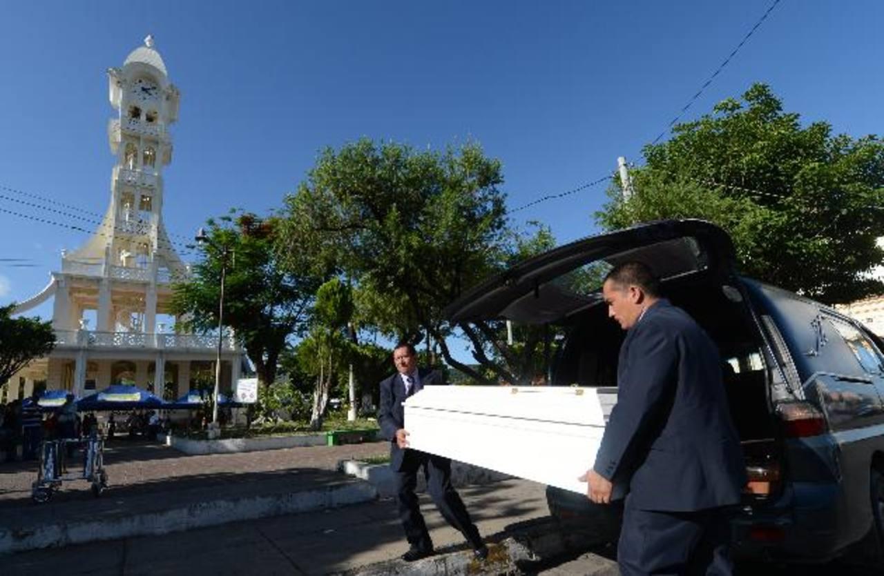 Empleados de una funeraria trasladan el féretro a la torre del parque central de San Vicente. Foto EDH / Douglas Urquilla.