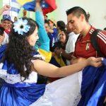 Una de las peregrinas salvadoreñas enseña un baile a un joven venezolano. foto edh