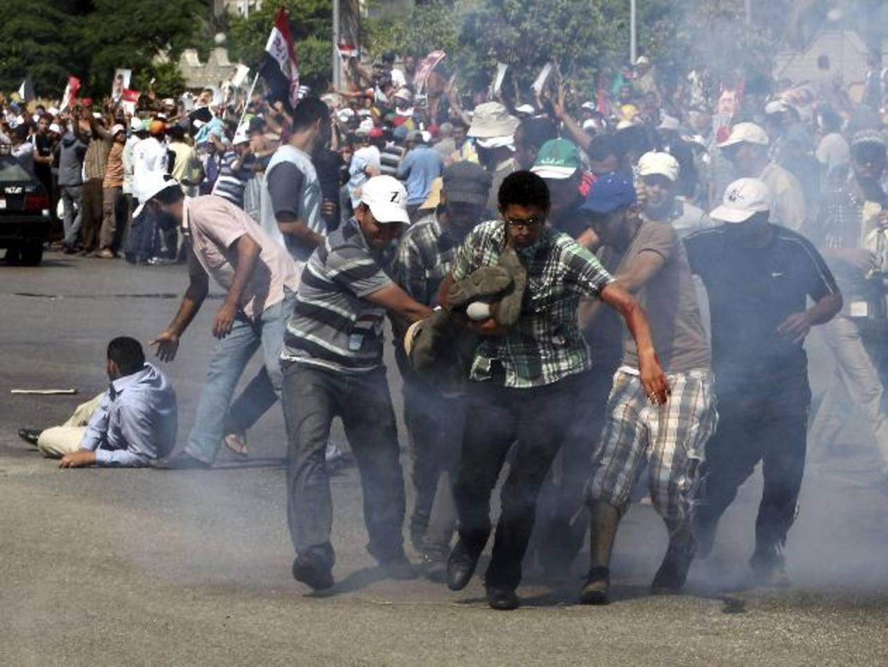 Simpatizantes de Mursi trasladan a un herido durante una manifestación. foto edh / EFE