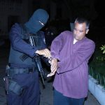 Un agente policial esposa a uno de los 16 detenidos durante el operativo realizado la madrugada de ayer en varios municipios del departamento de San Vicente. Foto / Cortesía FGR