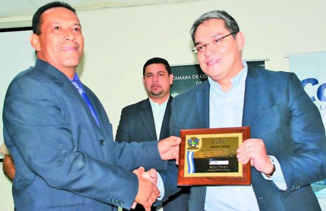 Boris Quintanilla (derecha) fue el encargado de recibir el reconocimiento de la Cámara de comercio que fue entregado por Raúl Castro. Atrás el edil Ezequiel Milla. FOTO EDH/Insy Mendoza