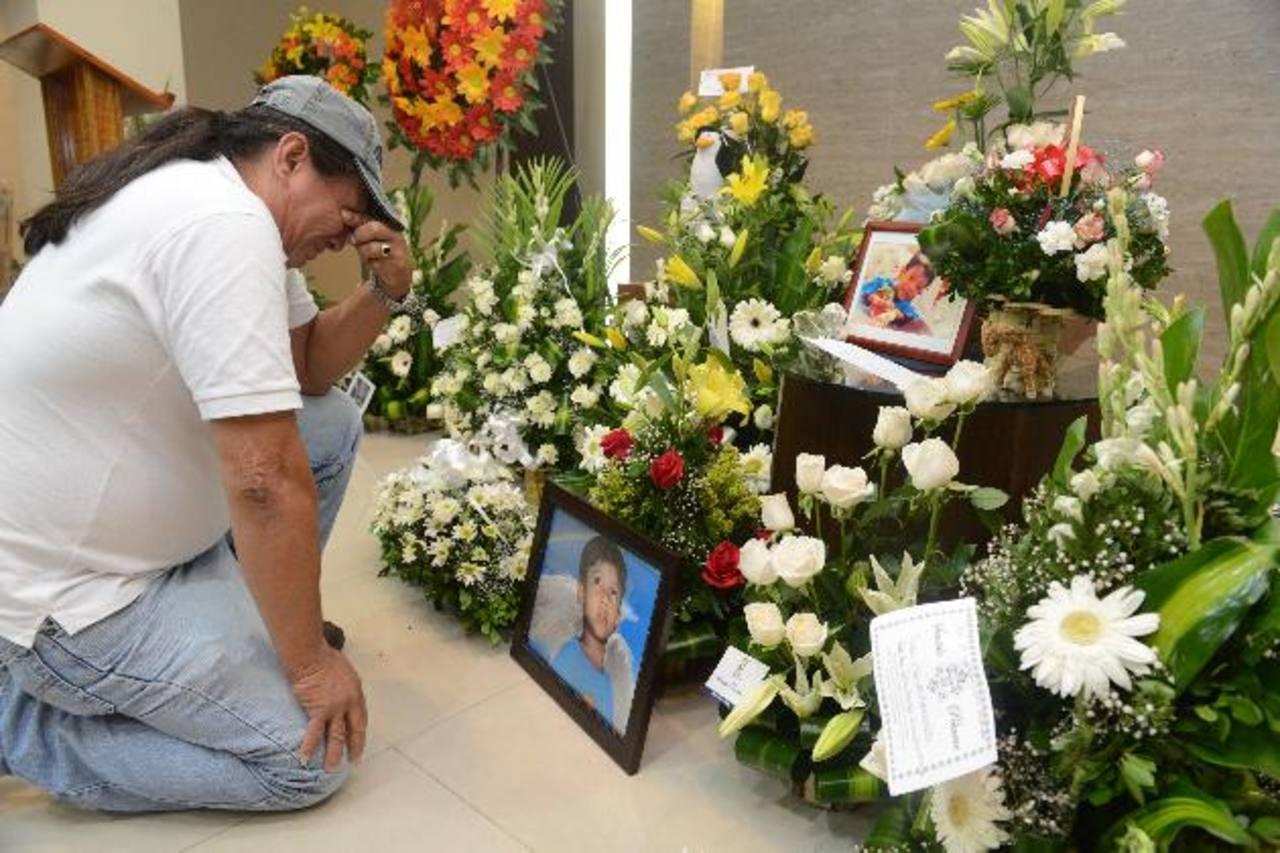 Óscar Waldemar López ora frente a la foto de su hijo, mientras familiares y amigos se concentran en la sala de velaciones en esta capital. fotos edh / miguel villalta