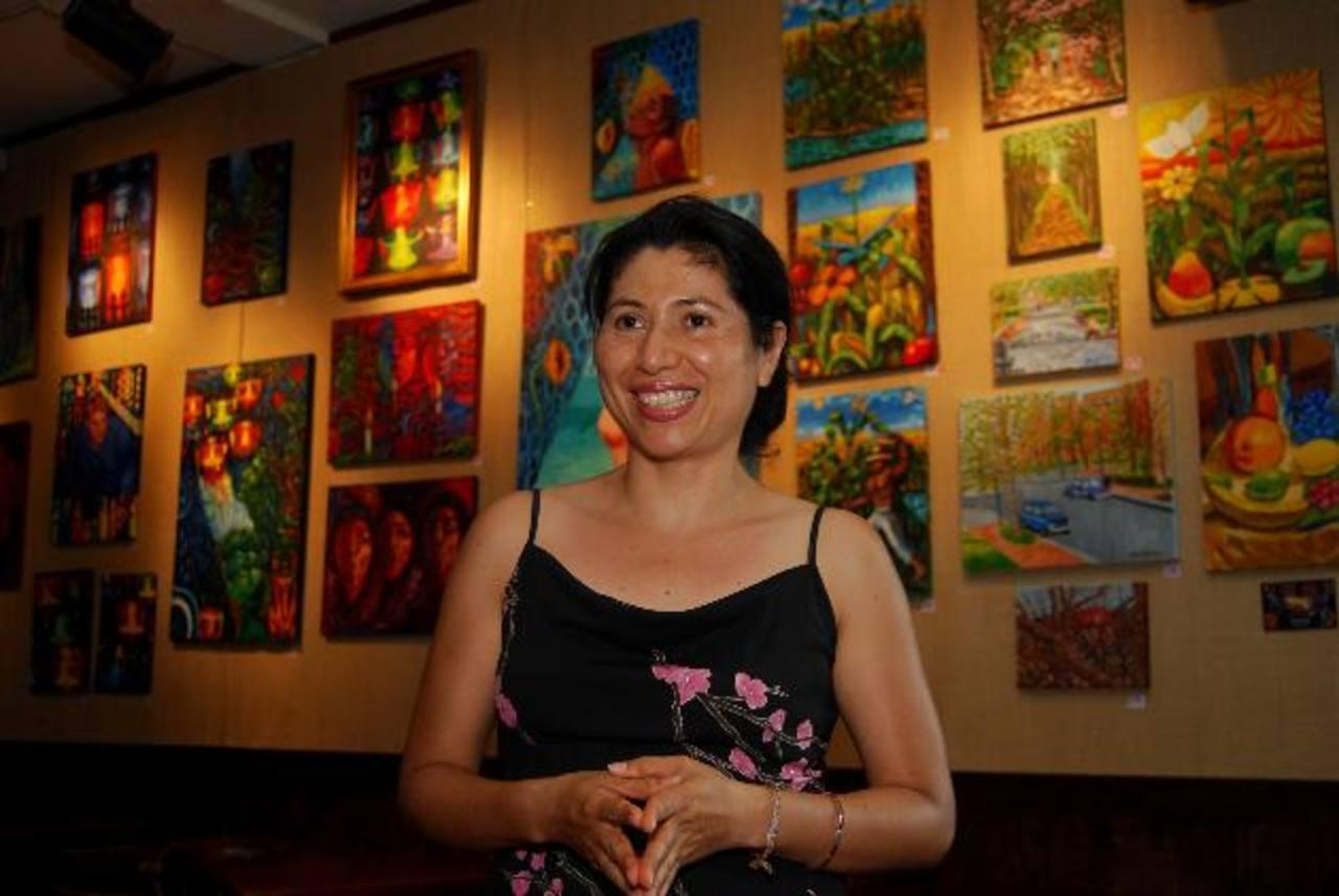 La artista plástica con una panorámica de algunas de las 33 obras en exposición. Fotos EDH