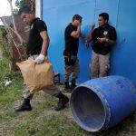 Policías custodian el barril y evidencia donde estaba el cuerpo de un joven en Ilopango. Foto EDH / E. Chávez