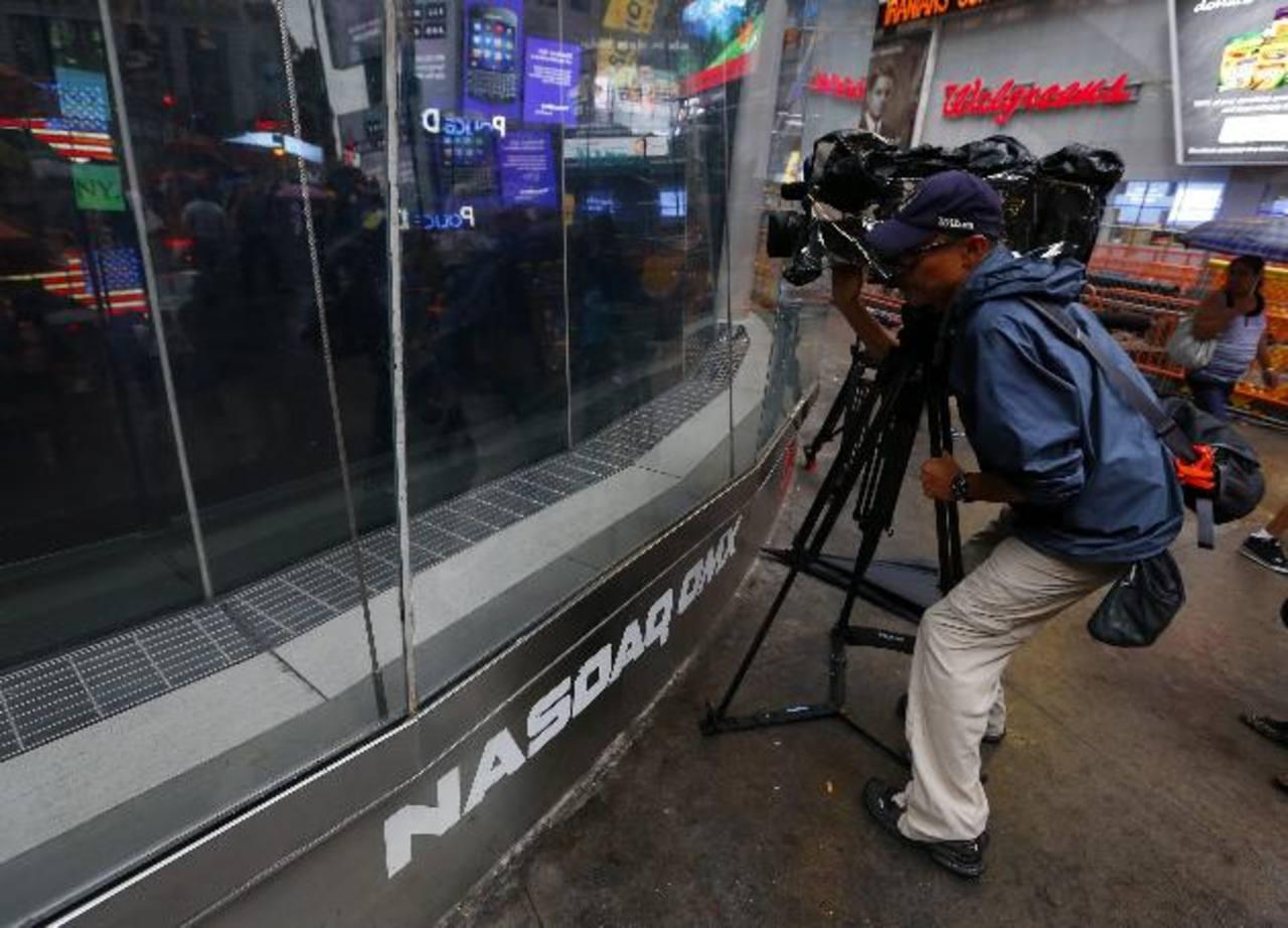 Un camarógrafo trata de captar imágenes del apagón del Nasdaq. El índice es operado por Nasdaq OMX Group.