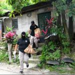 Policías abandonan la casa donde ayer hallaron uniformes policiales. La zona es asediada por maras. Foto EDH / René Estrada