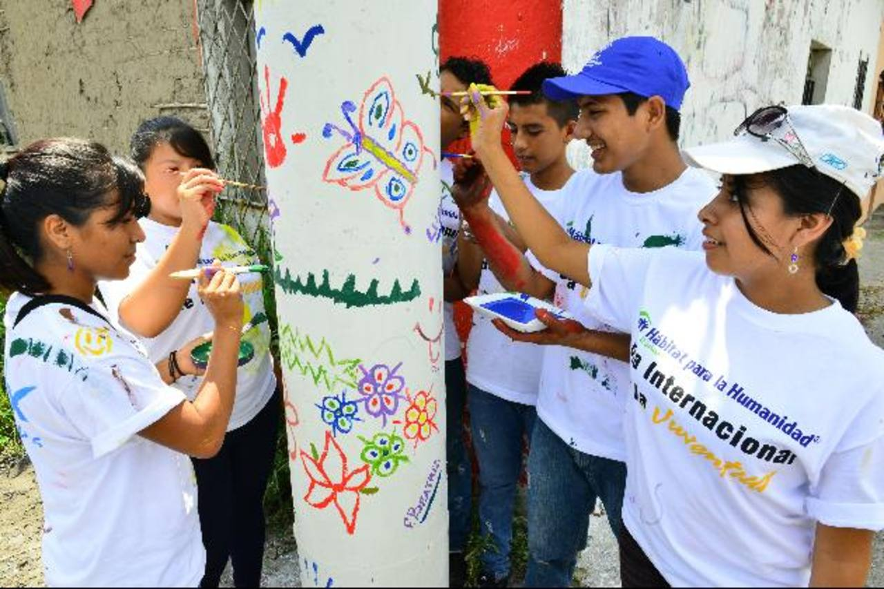 Jóvenes originarios de diferentes lugares del municipio participaron desde primeras horas de la mañana en la jornada de pintura de murales en postes y casas de la ciudad. Foto EDH / César Avilés