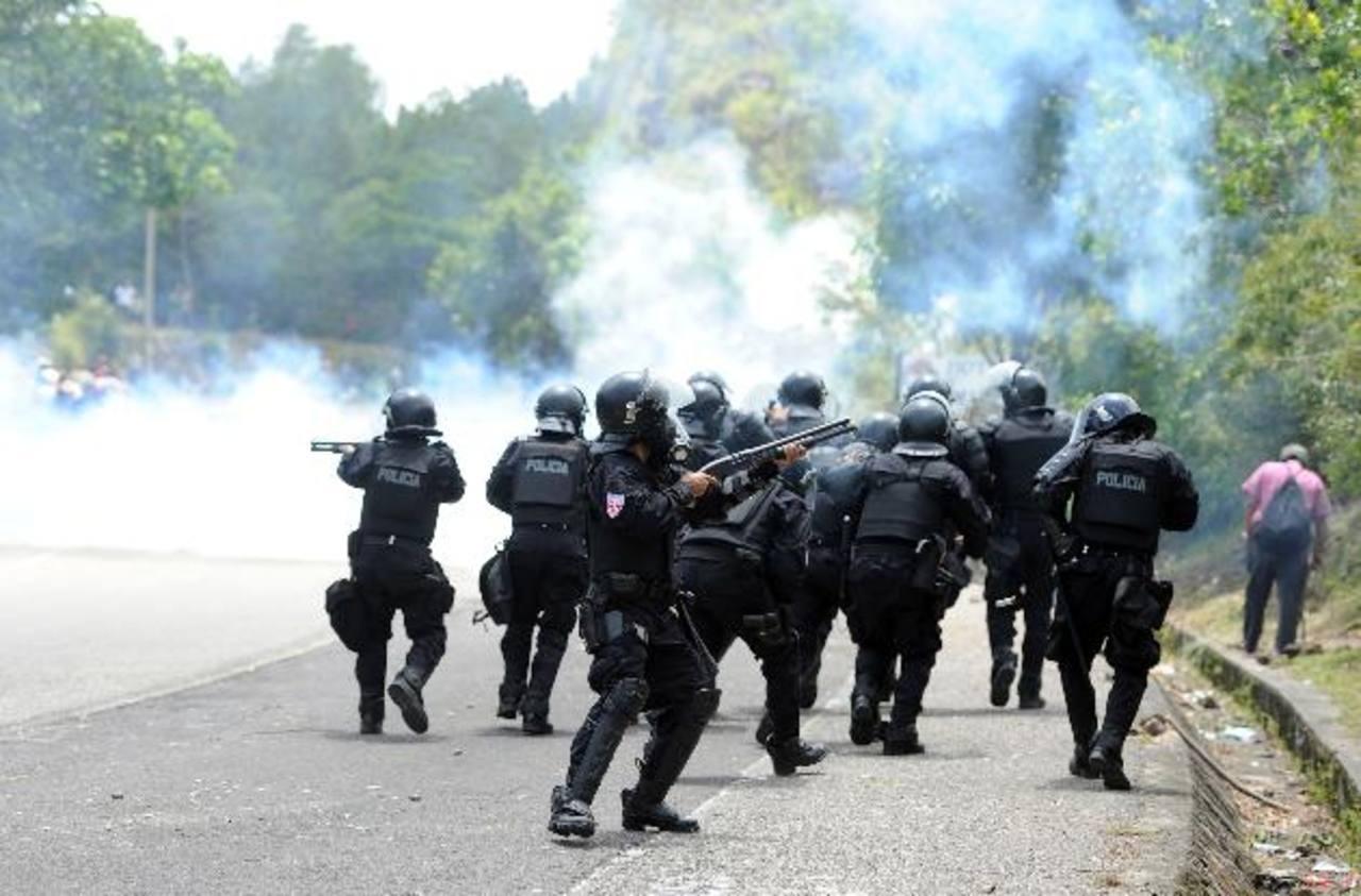 Agentes de la Unidad de Mantenimiento del Orden (UMO) dispersan a los excombatientes del ejército y del FMLN que protestaban en La Palma, Chalatenango. Foto EDH / Marlon Hernández