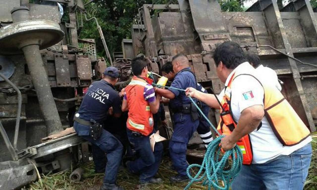 Socorristas tratan de liberar a uno de los indocumentados que está atrapado entre los hierros de uno de los vagones. Foto edh / efe
