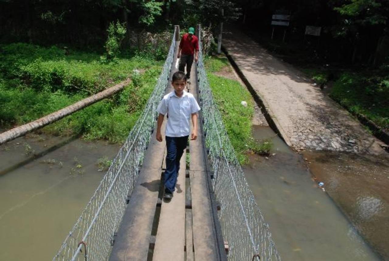 Los habitantes de la zona construyeron un puente de hamaca provisional, que también es inseguro. A un costado, a la izquierda, se observa el árbol de coco que usaron. Fotos EDH / CRISTIAN DÍAZ.