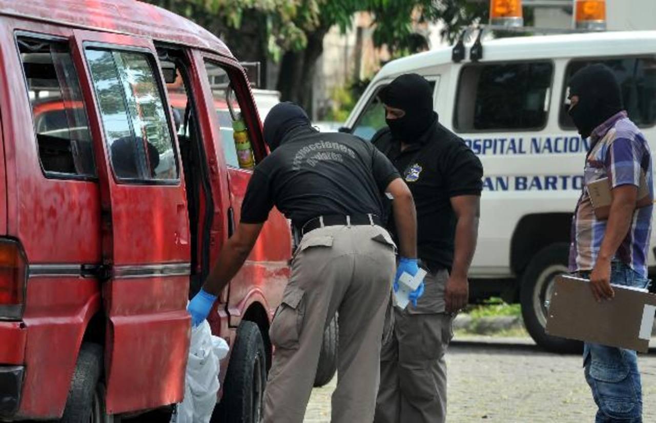 Policías inspeccionan el microbús donde quedó el cadáver de un pandillero que era trasladado hacia el hospital de San Bartolo. Dos más murieron en el hospital. Foto EDH / Ericka Chávez.