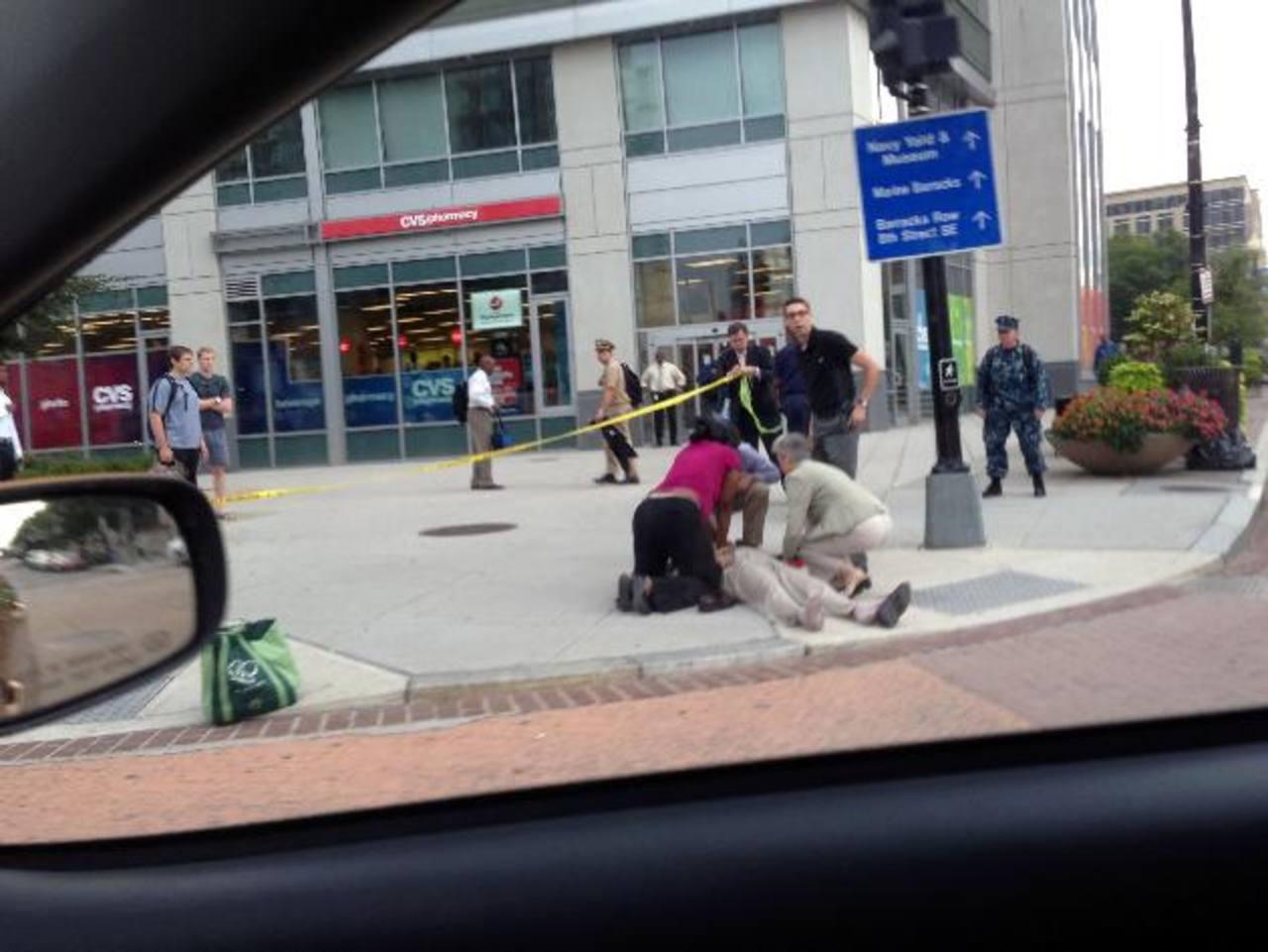 Una persona es atendida cerca de la zona donde un pistolero mató a unas 12 personas. foto edh / ap