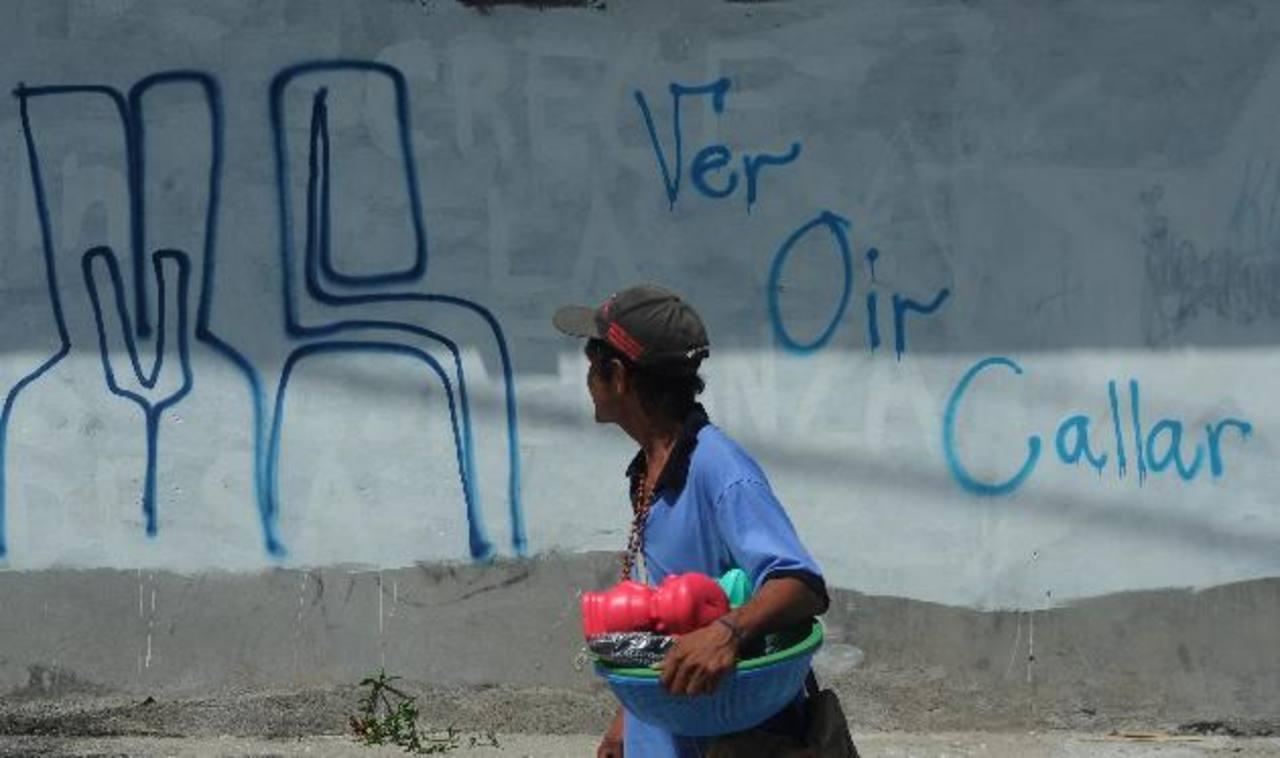 Una persona observa el MS que recién han pintado pandilleros en la colonia Vista Hermosa, en Cojutepeque. Fotos EDH