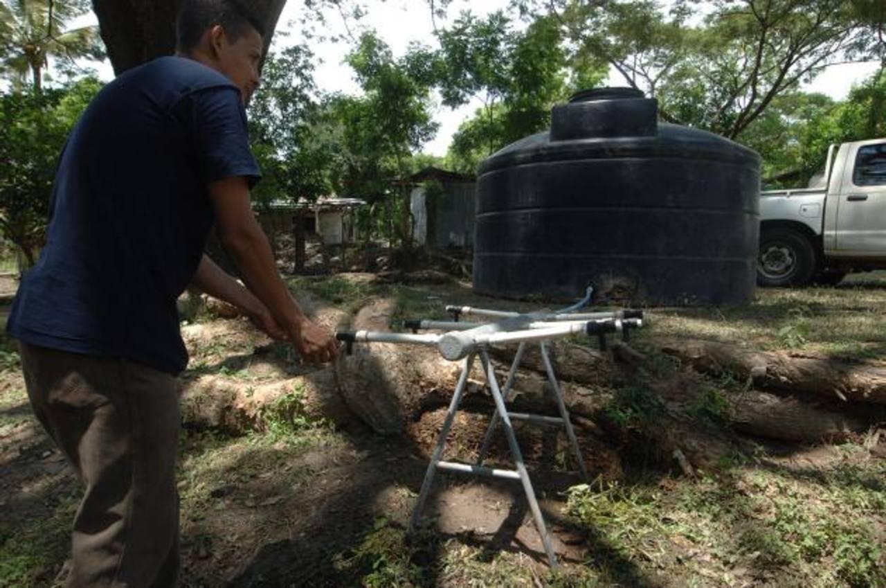 Residente toma agua proveniente de uno de los dos depósitos provisionales instalados. Foto EDH / Leonardo González