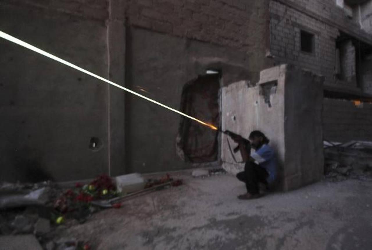 Un miembro del ejército libre sirio dispara desde una guarida en la zona de Deir al-Zor, en Siria. EE. UU. planea dotar de armas a los opositores al régimen de Assad. foto edh /Reuters