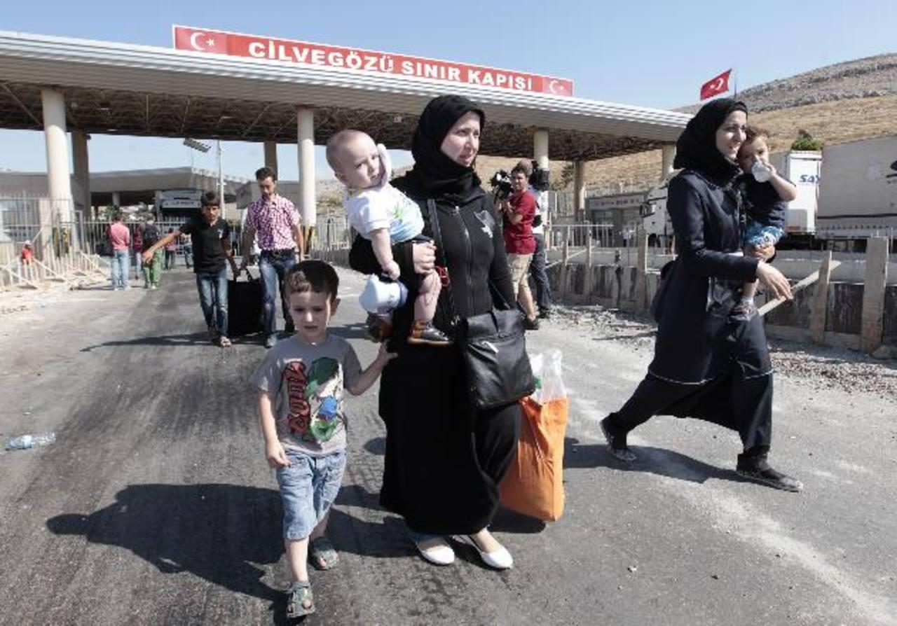 Refugiados sirios pasaban ayer por la puerta Cilvegozu, frontera turca. Más población está saliendo de Siria por la guerra.