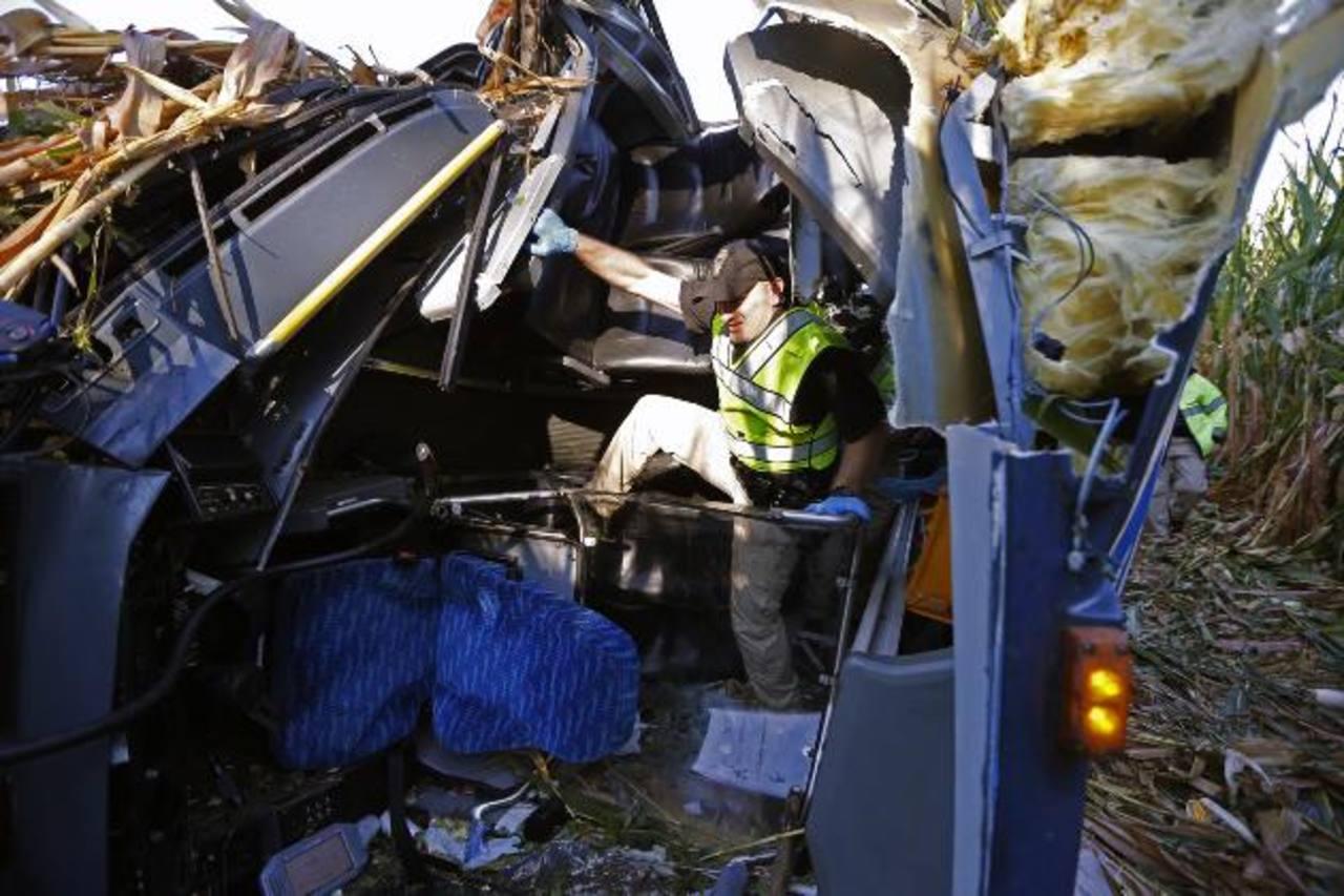Un investigador busca pistas del accidente entre los hierros retorcidos del bus que volcó ayer en Ohio. foto edh /AP