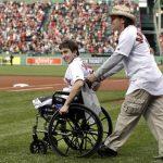 El sobreviviente del ataque con bombas al maratón de Boston Jeff Bauman es llevado en silla de ruedas por Carlos Arredondo. Foto/ AP