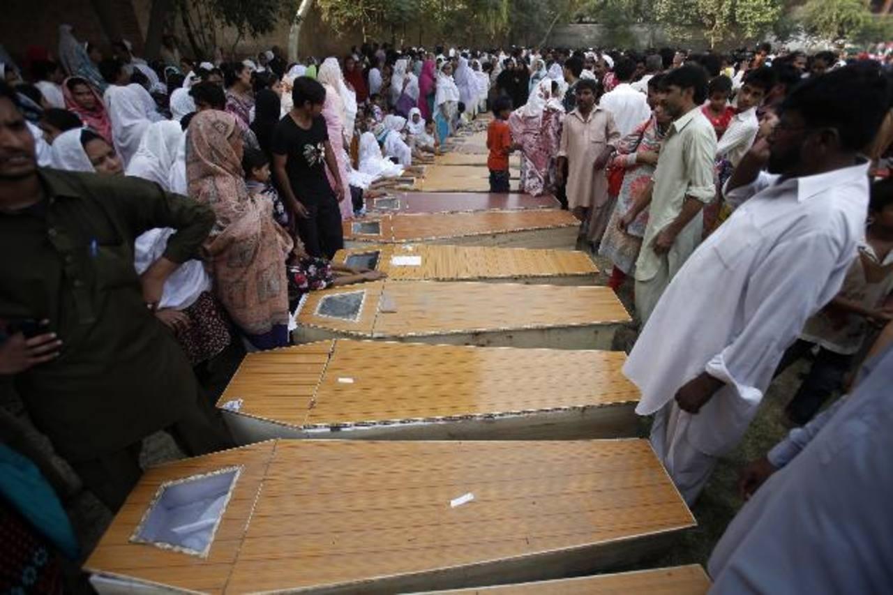 Cristianos lloran junto a los ataúdes de sus familiares, que murieron en un atentado suicida contra una iglesia. foto EDH /reuters