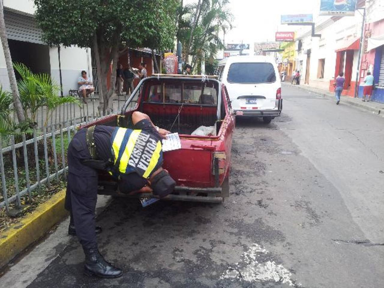 Agentes de la PNC retiran las placas a vehículos estacionados en sitios en los que no está permitido. Foto EDH / milton jaco