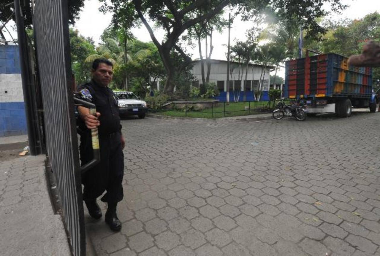 Un agente de la Policía abre el portón de la División Antinarcóticos (Dan), adonde llevaron a las siete personas detenidas.
