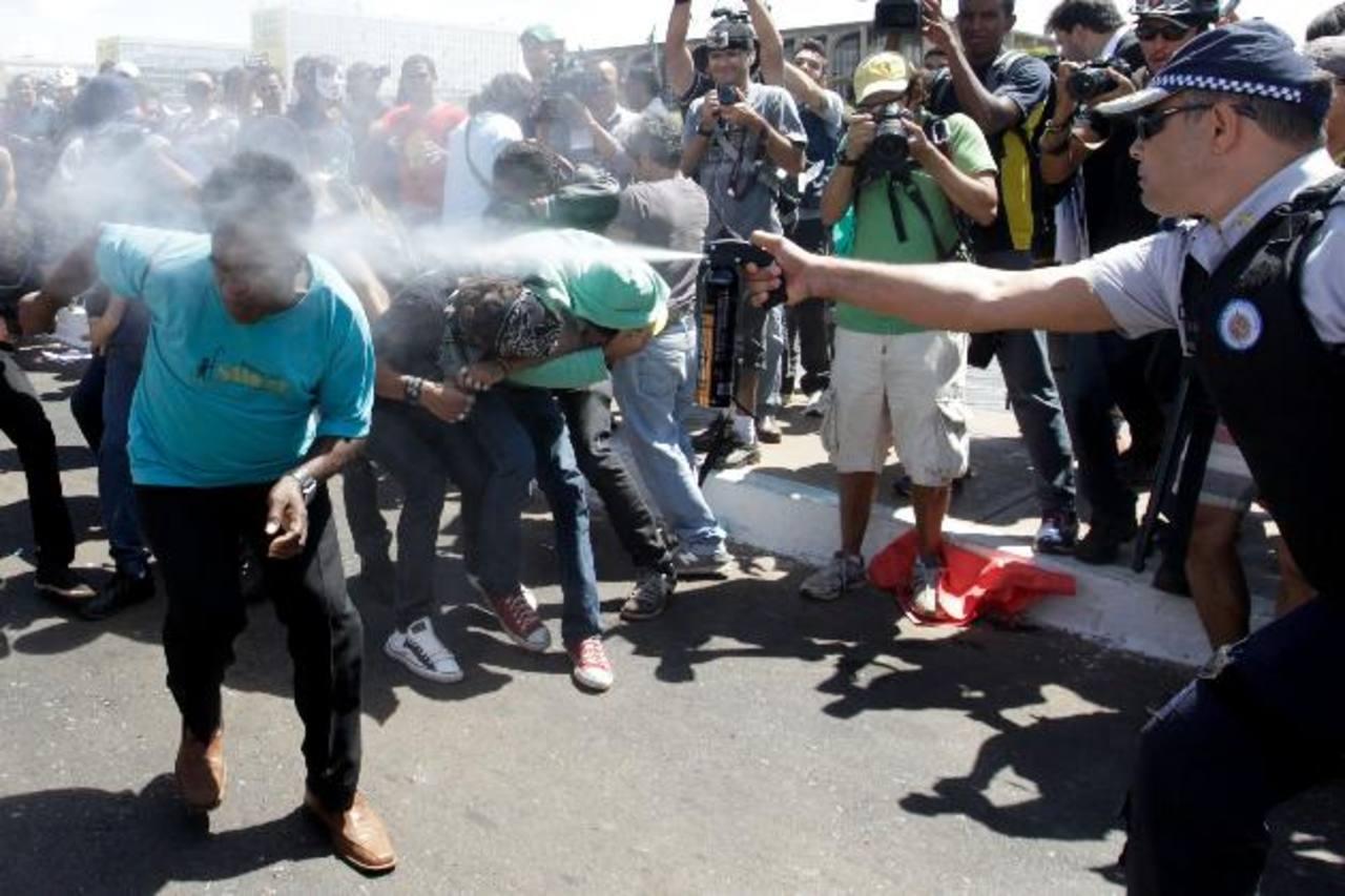 Manifestantes se enfrentaron ayer a la policía ayer frente al Congreso Nacional brasileño durante protestas en el desfile del Día de la Independencia. La policía les lazó gases. foto edh / EFE
