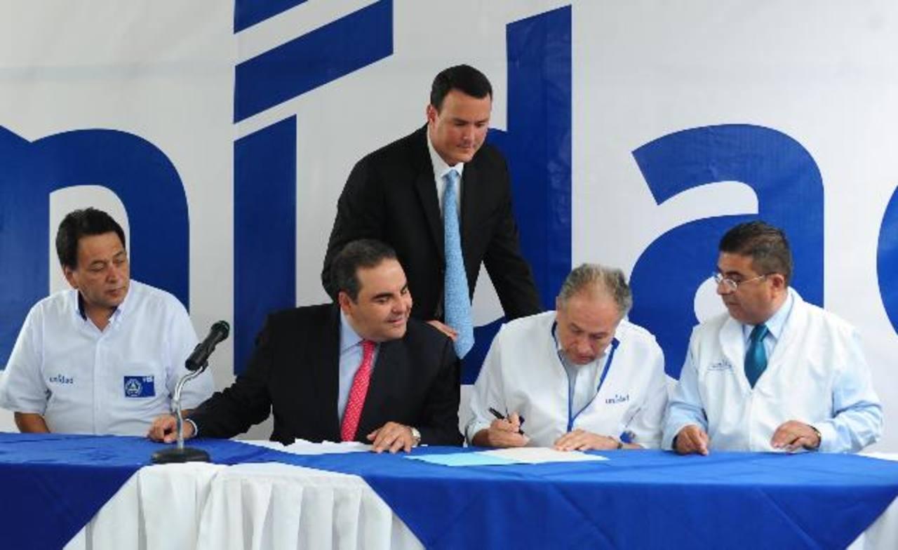 Manuel Rodríguez, del PCN, y el candidato Antonio Saca observan mientras Andrés Rovira, de Gana, firma el pacto de coalición. Foto EDH / Lissette Lemus