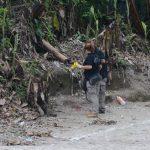 Dos investigadores policiales recolectan evidencias en la cancha donde fue el atentado. Foto EDH / Miguel Villalta