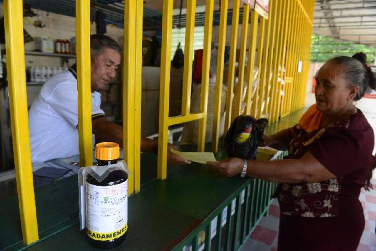 Heriberto Figueroa Chávez atiende a Santos, quien usa uno de los herbicidas recién prohibidos en su parcela. Fotos EDH / Miguel Villalta