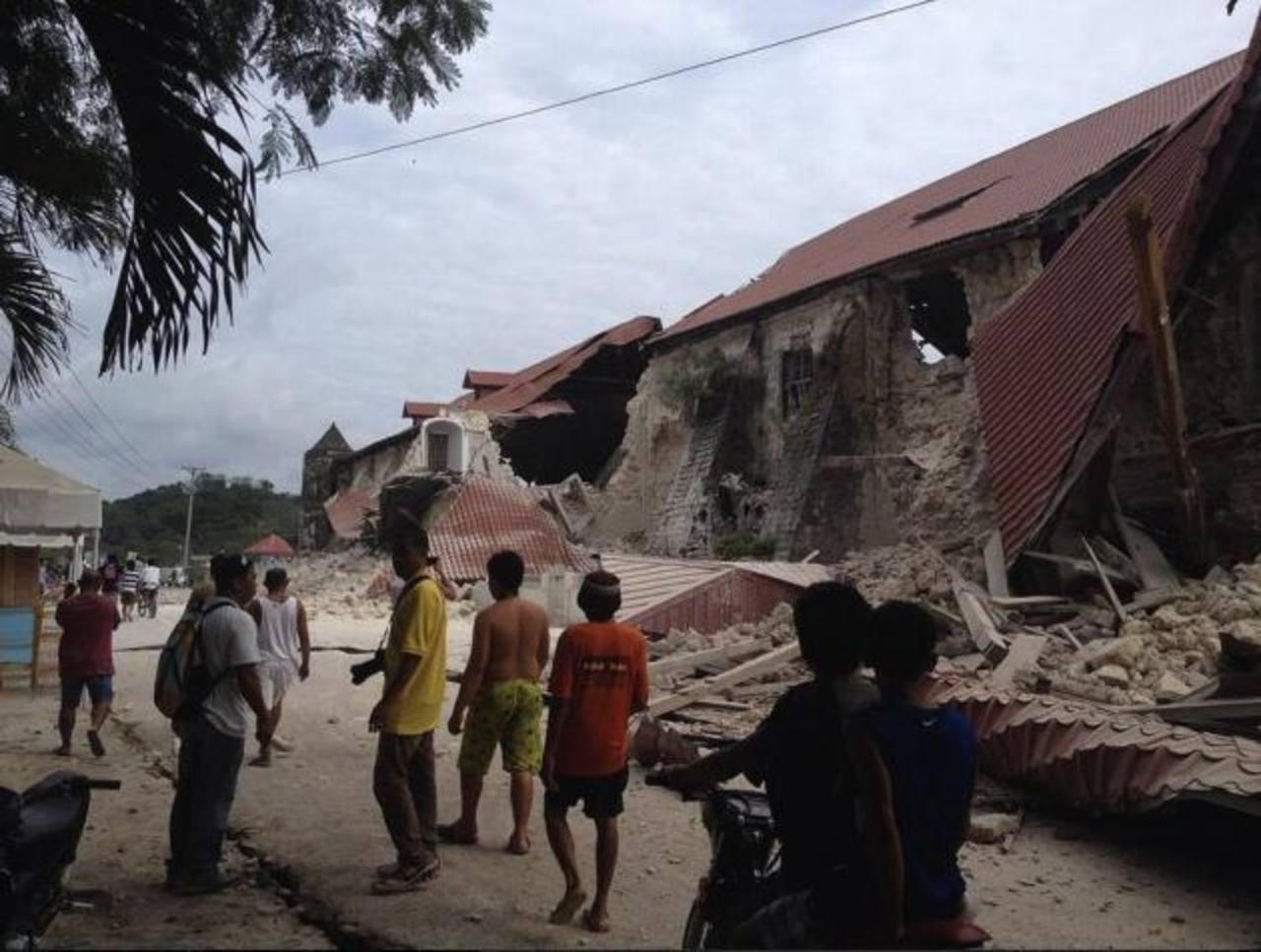 Filipinos observan la Catedral San Pedro destruida por el terremoto. foto edh / efe